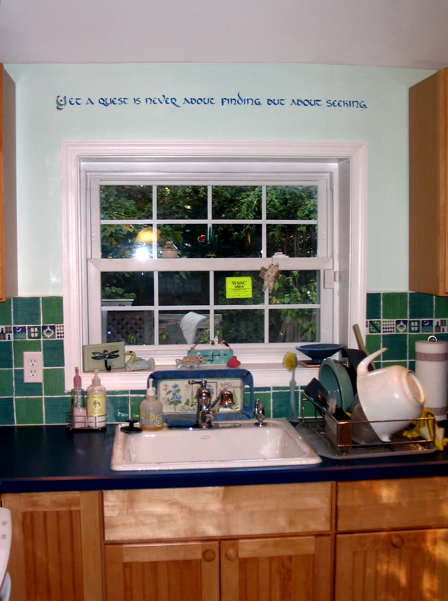 """Calligraphic inscription above the kitchen window of a Sligo Park Hills house: """"Yet a quest is never about finding, but about seeking."""""""