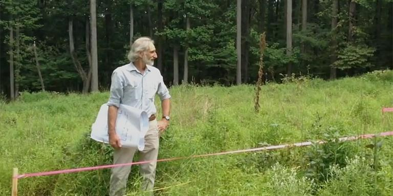 Alan surveys our newly staked lot prior to construction