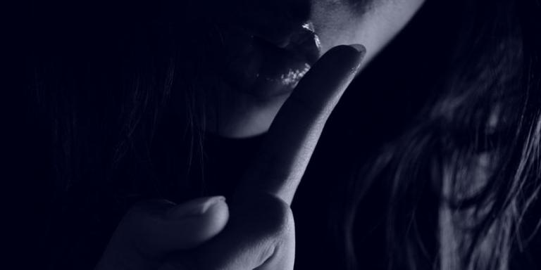 Woman holding a finger to her lips