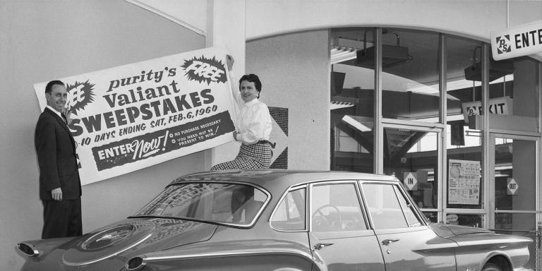 Harry and Carmen hang a poster for the Mancini Motors sweepstakes